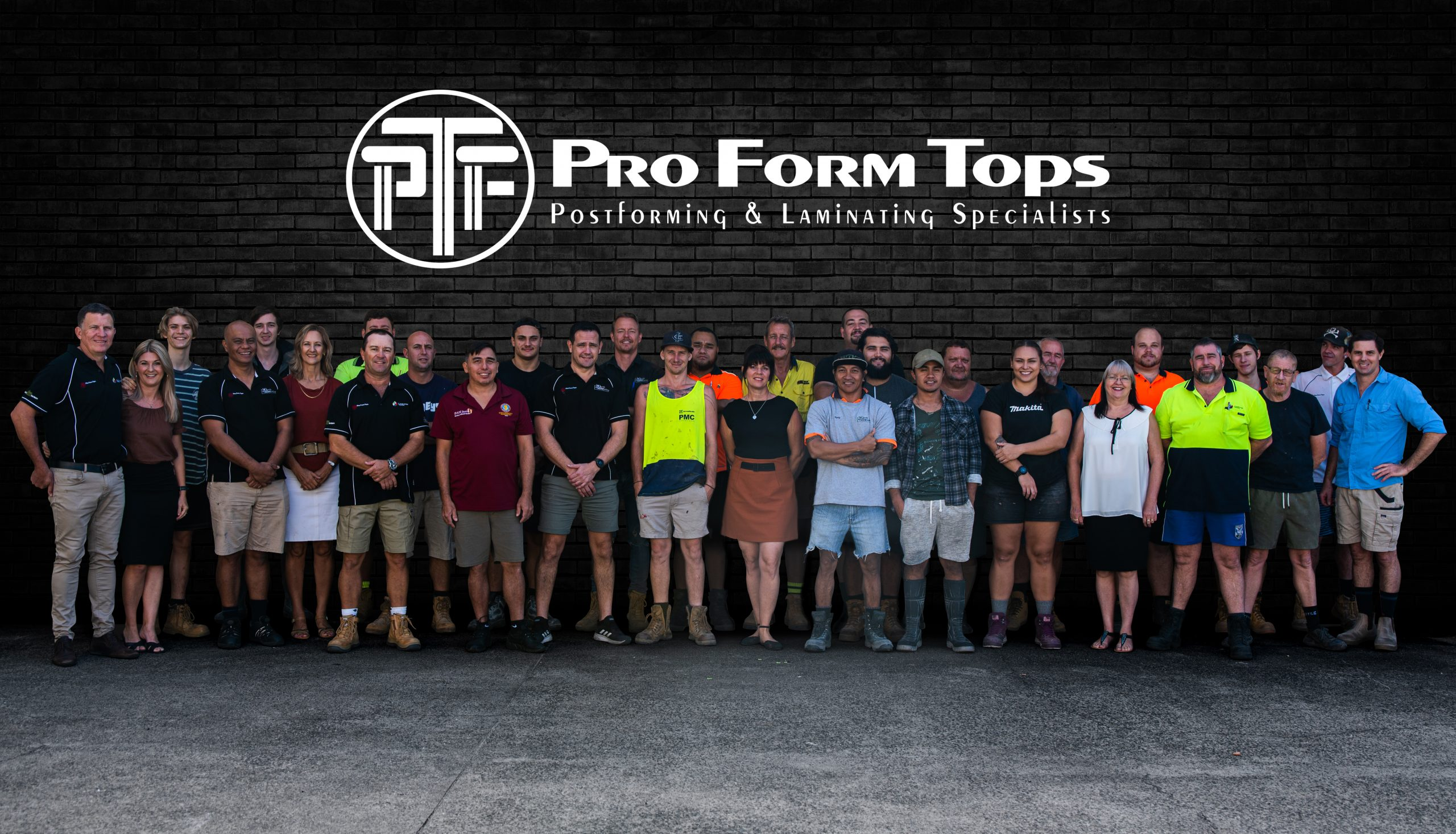 Photo of entire Pro Form Tops team. 31 people in total standing in a line of two rows. Pro Form Tops logo place above group.